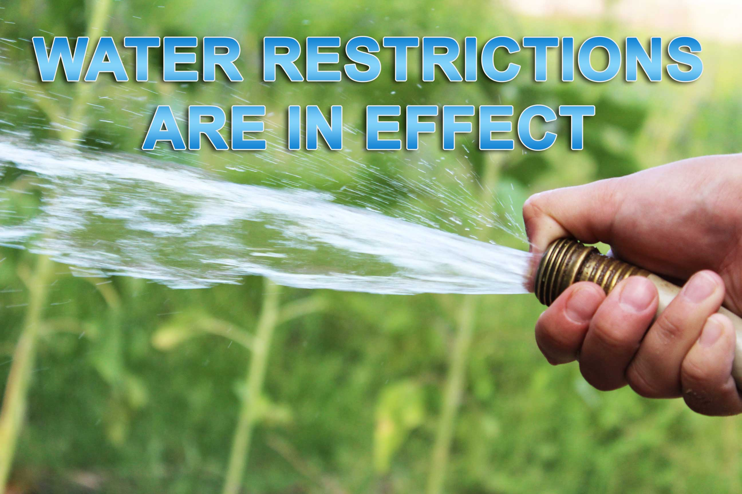 Hose spraying with overlayed message Water Restrictions are in Effect