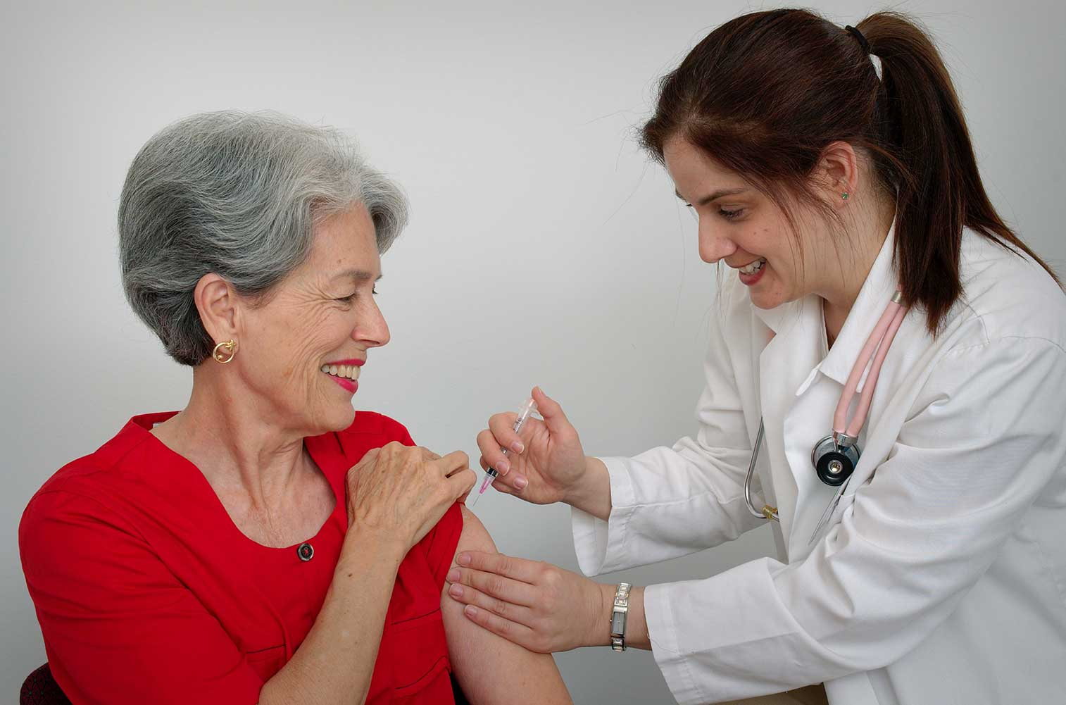 Senior woman receiving vaccination from her doctor.